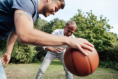 Father looking at basketball held by son in backyard - p300m2276995 by Gustafsson