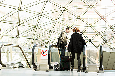 Business people moving down escalator in railroad station - p426m1085312f by Kentaroo Tryman