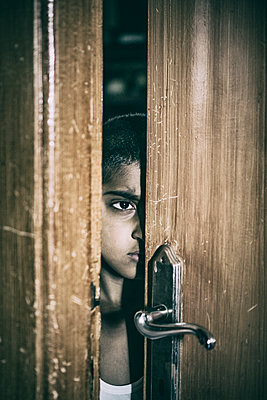 Boy looking through the door  - p794m1057121 by Mohamad Itani