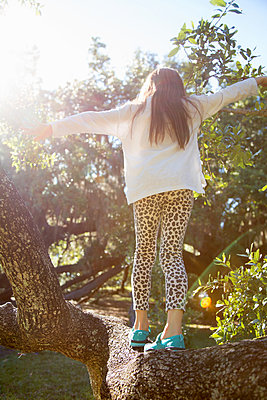 Rear view of girl walking on tree branch - p924m1513614 by Kinzie Riehm