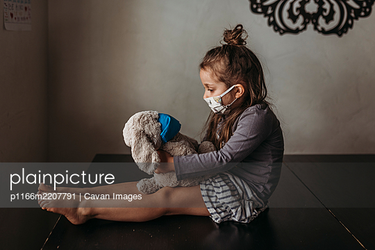 Side view of young girl with mask on sitting with masked animal - p1166m2207791 by Cavan Images