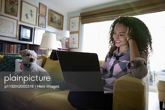 Smiling teenage girl with dog using laptop on sofa - p1192m2000316 by Hero Images