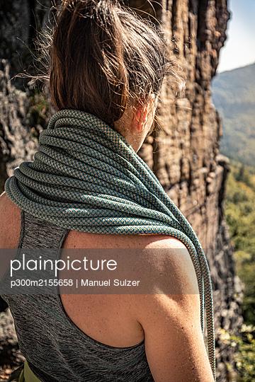 Woman preparing to climb, climbing rope around the neck - p300m2155658 by Manuel Sulzer