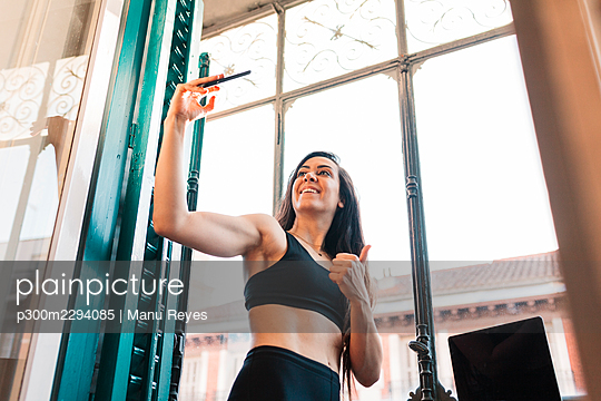 Smiling young woman showing thumbs up while taking selfie by window at home - p300m2294085 by Manu Reyes