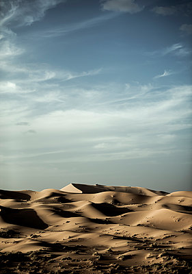 Desert landscape with sand dunes under a cloudy sky. - p1100m1482278 by Mint Images