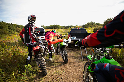 Male friends on motorbikes in rural field - p1192m1500157 by Hero Images