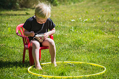 Little boy in red chair eating from a cup - p1418m2008130 by Jan Håkan Dahlström