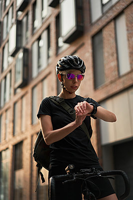 Woman cyclist looks at wristwatch on background of brick building in summer - p1630m2197080 by Sergey Mironov