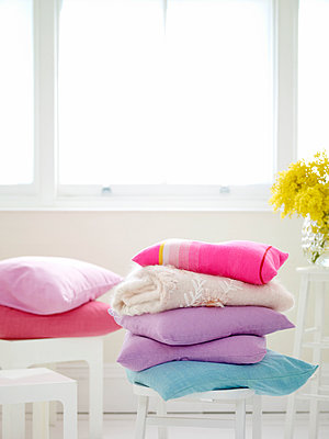 Stacked pastel cushions in bright interior - p349m2167713 by Polly Wreford