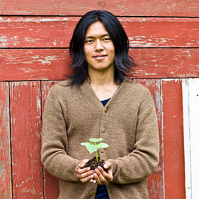 Japanese man holding potted plant outdoors - p555m1305875 by Jed Share/Kaoru Share