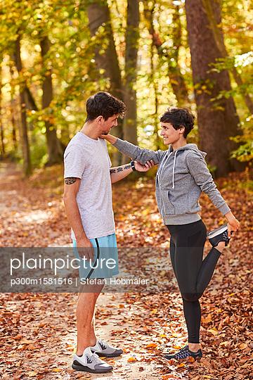 Couple stretching in autumn forest - p300m1581516 von Stefan Hobmaier