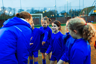 Girls soccer team listening to coach in huddle - p1023m2035198 by Paul Bradbury