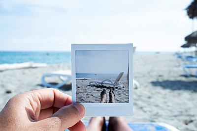 Mann mit Foto am Strand - p1423m2020599 von JUAN MOYANO
