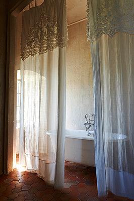 Vintage bathtub behind curtain - p1629m2211356 by martinameier