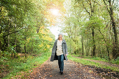 Portrait of happy woman walking in the forest in autumn - p300m1537405 by Robijn Page
