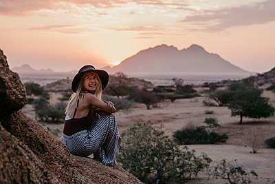 Namibia, Spitzkoppe, laughing woman sitting on a rock at sunset - p300m2080839 by letizia haessig photography
