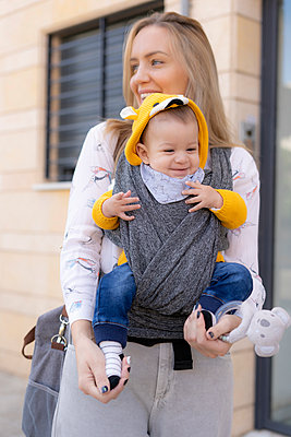 Happy mother carrying baby boy in a sling outdoors - p300m2154765 by Eloisa Ramos