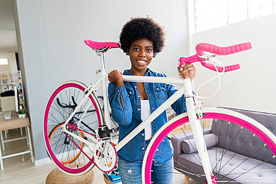 Smiling young woman carrying bicycle at home - p300m2275903 by Giorgio Fochesato
