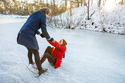 Boyfriend holding hands of girlfriend while getting up on frozen lake - p300m2287647 by Frank van Delft