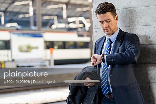 Businessman checking the time at train station - p300m2102928 von Daniel Ingold