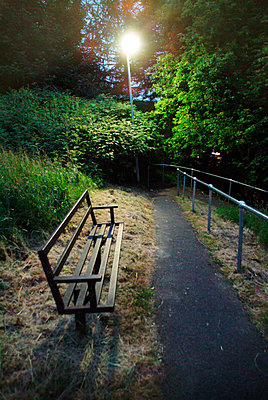 Elevated view of a footpath and bench at night with a bright street light - p1072m830461 by Stephen Cliffe
