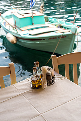 Table in Greek taverna by the waterfront with a fishing boat in the background. - p1433m1526040 by Wolf Kettler