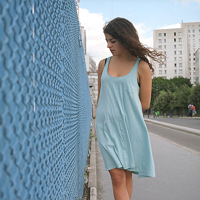 A girl wearing a blue dress standing next to a blue fence - p1610m2185278 by myriam tirler