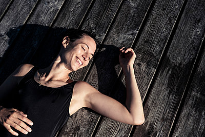 Happy woman wearing black swimsuit lying on a jetty - p300m2156858 by Wilfried Feder