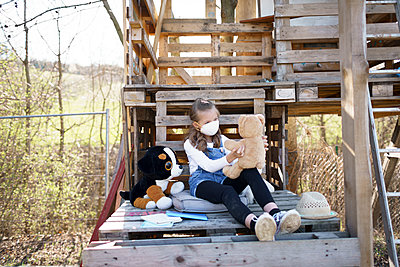 Girl with protective mask sitting in the garden at tree house and playing alone with her cuddly toys during the corona quarantine - p300m2180242 by Epiximages