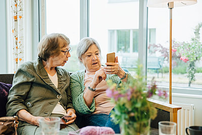Elderly woman using mobile phone while sitting with female friend on sofa against window at retirement home - p426m2149326 by Maskot