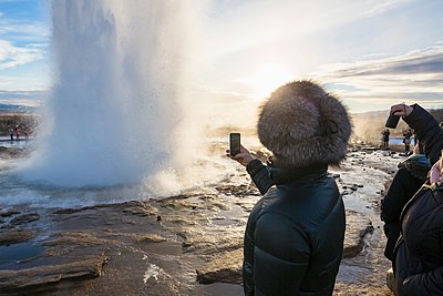Woman photographing The Great Geysir, a geyser that lies in the Haukadalur valley on the slopes of Laugarfjall hill, South West Iceland - p429m1105655 by dotdotred