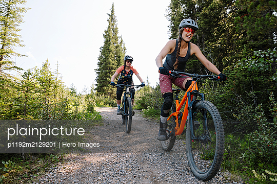 Women mountain biking on trail in woods - p1192m2129201 by Hero Images