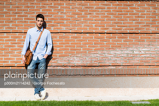Young man leaning on wall in the city - p300m2114242 von Giorgio Fochesato
