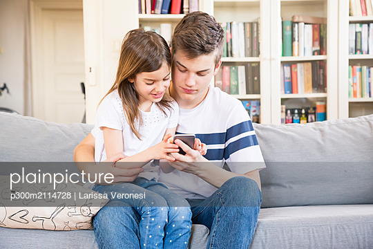 Teenage boy sitting with his little sister on the couch at home looking at cell phone - p300m2114728 by Larissa Veronesi