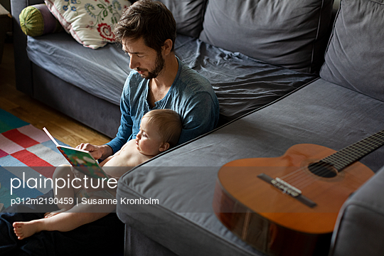 Father reading book to baby - p312m2190459 by Susanne Kronholm