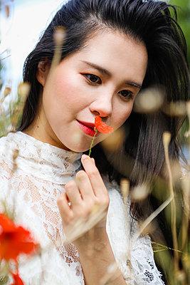 Asiatin richt an Mohnblume - p045m2204315 von Jasmin Sander
