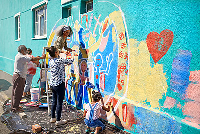Community volunteers painting multicolor mural on sunny urban wall - p1023m2066870 by Trevor Adeline