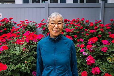 Senior woman wearing eyeglasses standing in front of red flower garden - p1166m2285603 by Cavan Images