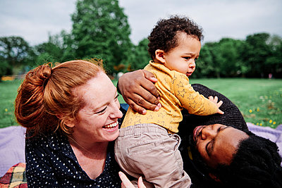 Multi-ethnic family enjoying with son at park - p300m2287372 by Angel Santana Garcia