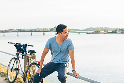 Sweden, Blekinge, Karlskrona, Man sitting on railing by lake - p352m1187347 by Karin Enge Vivar
