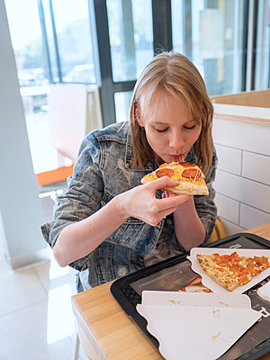 Young woman eating a pizza a pizzeria - p390m2149794 by Frank Herfort