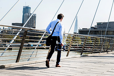 Businessman carrying scooter, Hungerford Bridge, London, UK - p429m1418030 by Bonfanti Diego