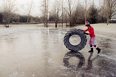 Woman rolling tyre on frozen lake - p924m1230234 by Pete Saloutos