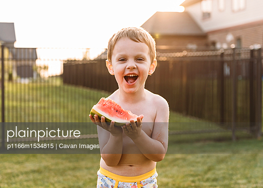 Portrait of cheerful boy eating watermelon at backyard - p1166m1534815 by Cavan Images