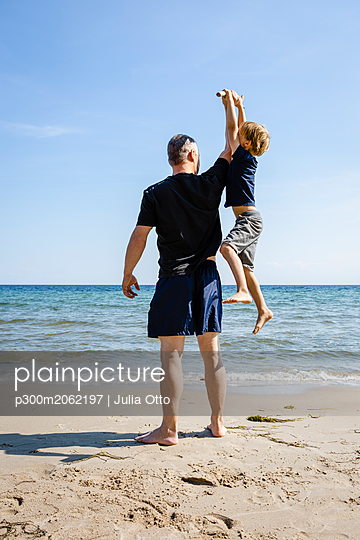 Father and son playing at the beach - p300m2062197 von Julia Otto