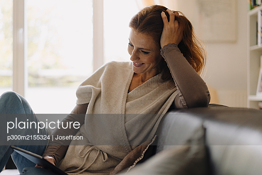 Smiling woman sitting on couch, using digital tablet - p300m2155324 by Joseffson