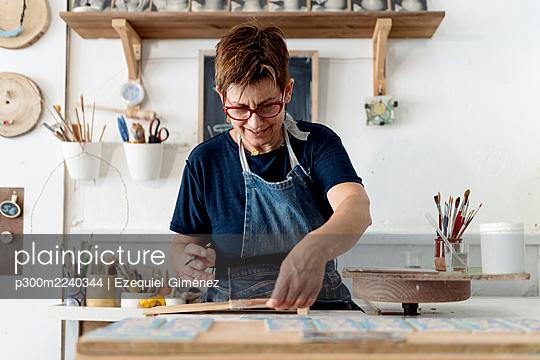 Mature female craftsperson working in ceramics store - p300m2240344 by Ezequiel Giménez