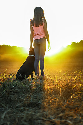 Teenage Girl and her Dog at sunset - p1019m1487239 by Stephen Carroll