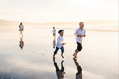 Boys running with mom at the beach - p1166m2073870 by Cavan Images