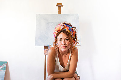 Portrait of young female painter in art studio next to empty canvas - p300m2103342 by Sus Pons